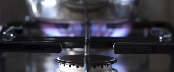 Close up of a gas hob with a pan on the back burner, shallow DOF.